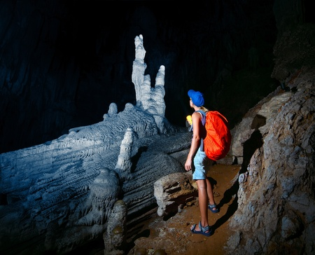 caving: Young woman with backpack exploring cave with torch