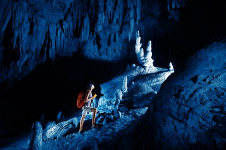 cave exploring: Young woman with backpack exploring huge cave with torch