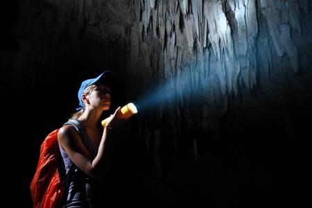 cueva: Mujer joven con mochila explorar la cueva con soplete