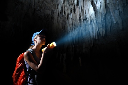 alone in the dark: Young woman with backpack exploring cave with torch