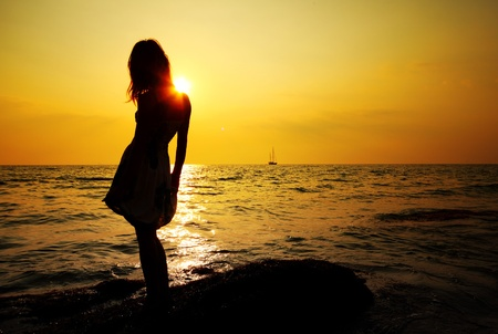 Young woman standing on rock in sea and looking to a sun photo
