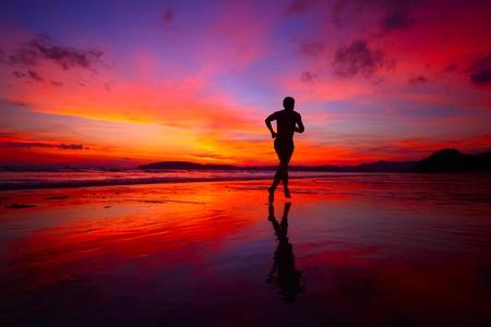 생생한 일몰 배경에 바다 가장자리로 젖은 모래에 조깅 젊은 남자