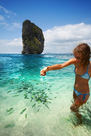 Young woman feeding sea fish standing in transparent blue water Stock Photo - 9633911