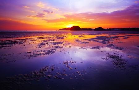 puesta de sol: P�rpura puesta de sol en una playa durante la marea baja