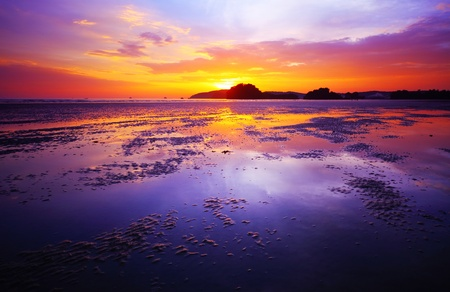 outflow: Purple sunset over a beach during low tide