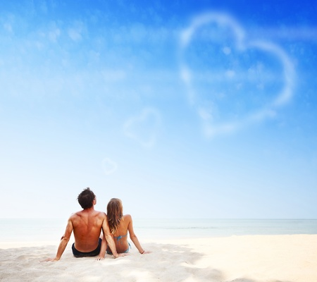 Young family sitting on warm sand by a sea and looking to a blue sky with heart shaped clouds Stock Photo - 9633862