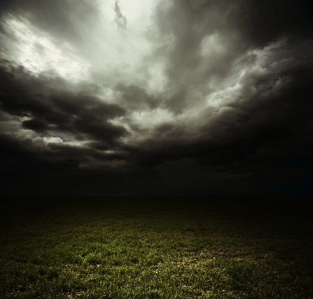 oscuro: Oscuras nubes de tormenta sobre Prado con pasto verde