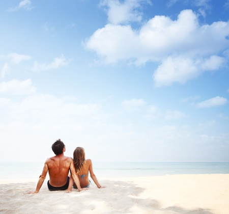 somewhere: Young man and woman sitting on warm sand by a sea and looking to somewhere