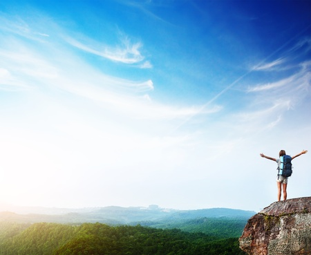 mountain top: Young woman with backpack standing on cliffs edge with raised hands and looking to a sky Stock Photo