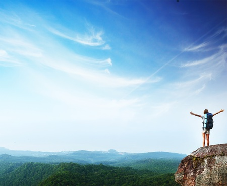mountain view: Young woman with backpack standing on cliffs edge with raised hands and looking to a sky Stock Photo