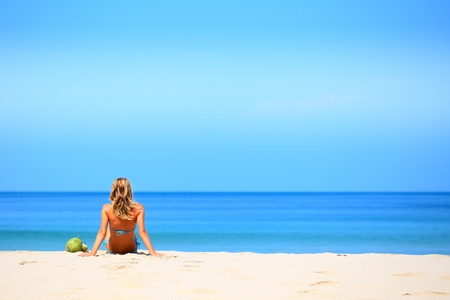 Young woman sitting on sand and looking to a sea photo