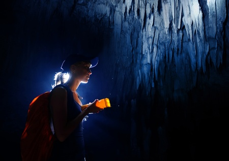 cave exploring: Young woman with backpack exploring cave with torch