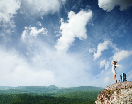 Young woman with backpack standing on cliffs edge with raised hands and looking to a sky photo