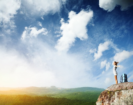 top of mountain: Young woman with backpack standing on cliffs edge with raised hands and looking to a sky Stock Photo