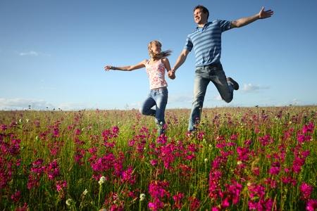manos levantadas al cielo: Rinning de hombre y mujer joven en pradera de campo con flores rosas