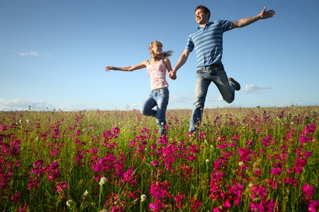 Young man and woman rinning on countryside meadow with pink flowers
