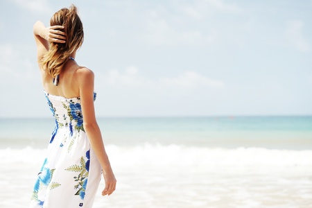 looking: Young woman in summer dress standing by blue sea and looking to horizon