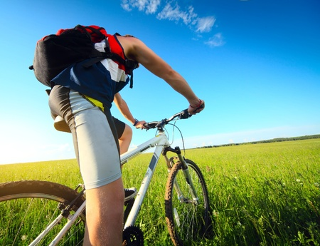 Young man riding on a bicycle on green meadow with a red backpack Stockfoto