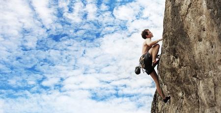 bergbeklimmen: Jonge man klimt op een klif over de blauwe hemel achtergrond