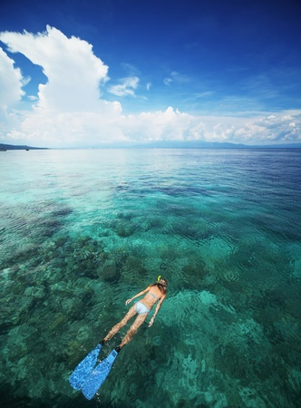 Young woman snorkeling in transparent shallow sea above coral reef. photo