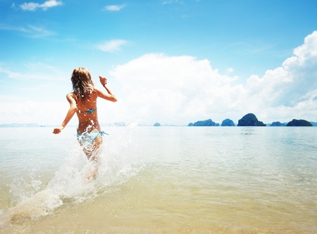 hight: Young woman hight speed running into sea with splashes
