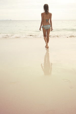 Young woman walking on wet perfect sand and going to swim in a sea  photo