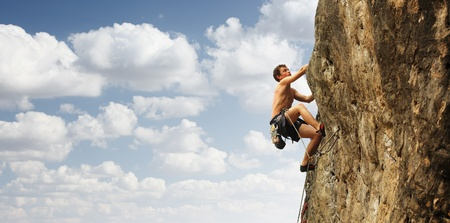 stijger: Jonge man klimt op een rots over de blauwe hemel achtergrond