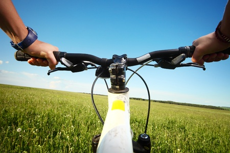 Riders hands holding handlebar on a green meadow photo