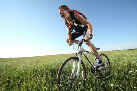 Young roaring man riding on bycycle through deep grass with exertion photo