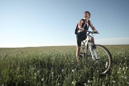 Young smiling man standing on meadow with bicycle photo
