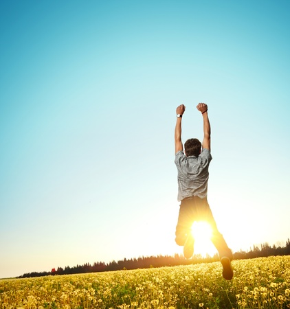 Young man jumping on meadow with dandelions on clear blue sky background Stock Photo - 9908415