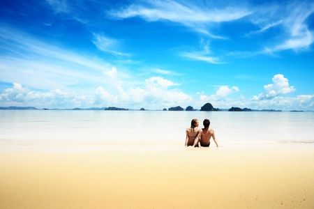 Young man and woman sitting on wet yellow sand of a tropical resort Stock Photo - 9912000