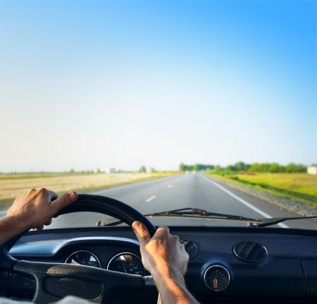manejando: Conductor de manos en un volante de un autom�vil retro durante cabalgando sobre una carretera de asfalto vac�a Foto de archivo