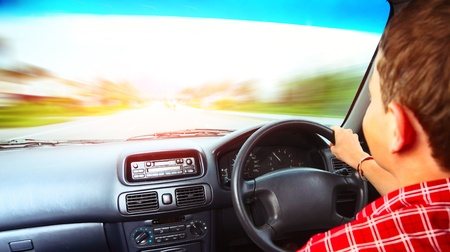 Young man driving a car on an urban asphalt road. Motion blurred road Stock Photo - 9912178