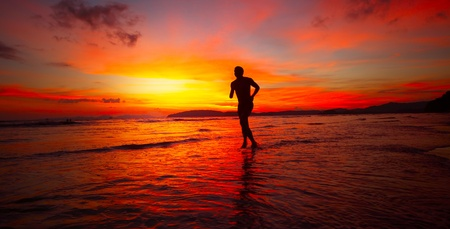 Young man running on wet coastline at bright sunset background Stock Photo - 9912185