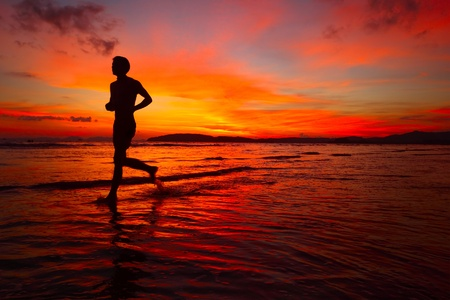 Young man running on wet coastline at bright sunset background Stock Photo