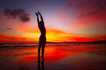 Young man doing exercises standing on wet sand at bright sunset background Stock Photo - 9912182
