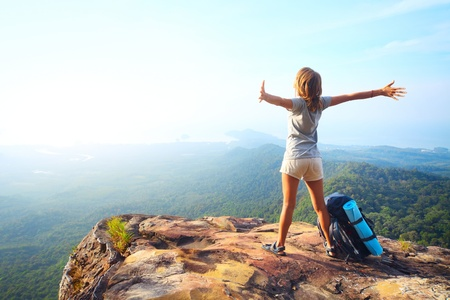 climbing: Young happy woman with backpack standing on a rock with raised hands and looking to a valley below Stock Photo