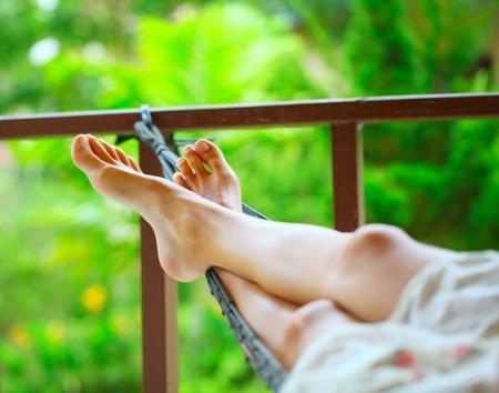 hamaca: Pies de una mujer joven tumbado en la hamaca en un jardín Foto de archivo