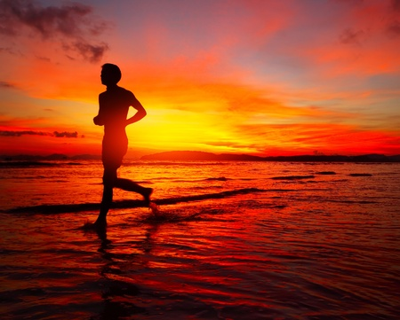 Young man running on wet coastline at bright sunset background photo