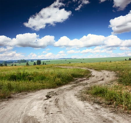 Rural dusty countryside road trough a fields with wild herbs and flowers photo