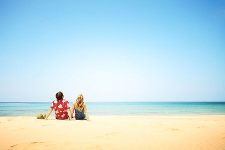 Young happy couple sitting on yallow sand by blue sea and looking to a clear sky photo