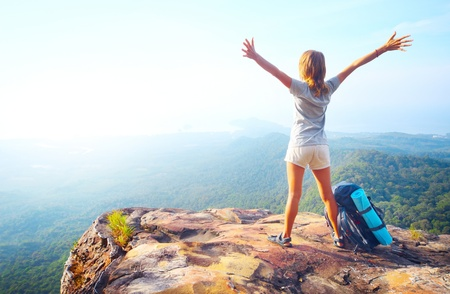 Young happy woman with backpack standing on a rock with raised hands and looking to a valley below Stock Photo