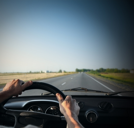 dash: Drivers hands on a steering wheel of a retro car during riding on an empty asphalt road Stock Photo