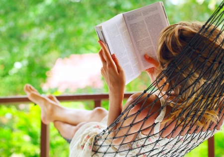 Young woman lying in hammock in a garden and reading a book. Shallow DOF. Focus on a left shoulder 스톡 콘텐츠