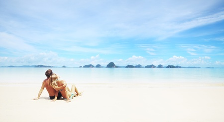 Young couple sitting on a resorts white sand and looking to a far islands on the horizon