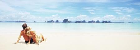 Pareja joven sentado en la arena blanca de un complejo y mirando a una medida de islas en el horizonte Foto de archivo - 43880086
