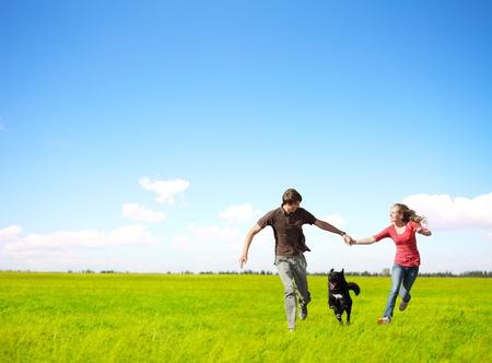 exteriores: Feliz pareja joven que se ejecuta en un prado verde con un perro