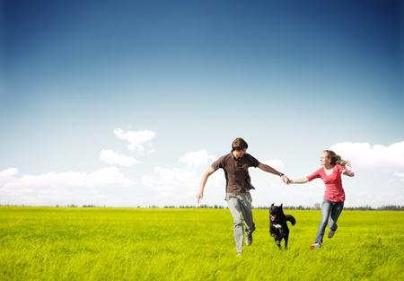 Jong gelukkig paar lopen op een groene weide met een hond