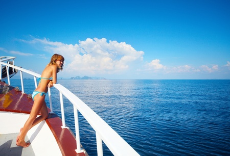 cruise travel: Young woman standing on a ships board and looking to a horizon